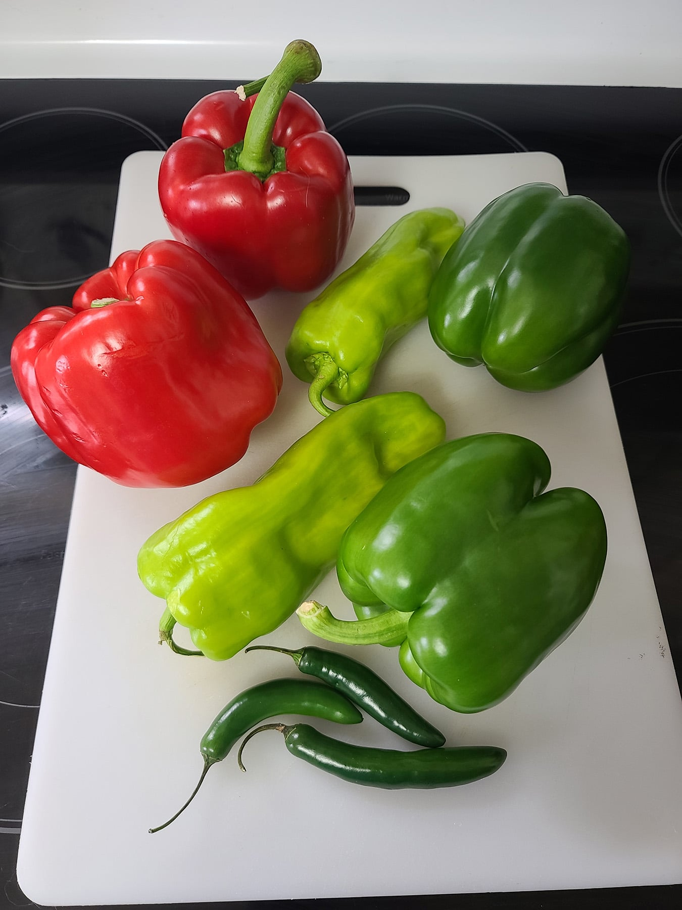 Several red and green peppers on a cutting board.