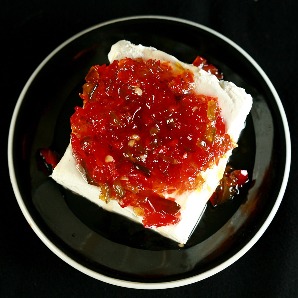 A mound of pepper jelly on a chunk of cream cheese on a small black plate.