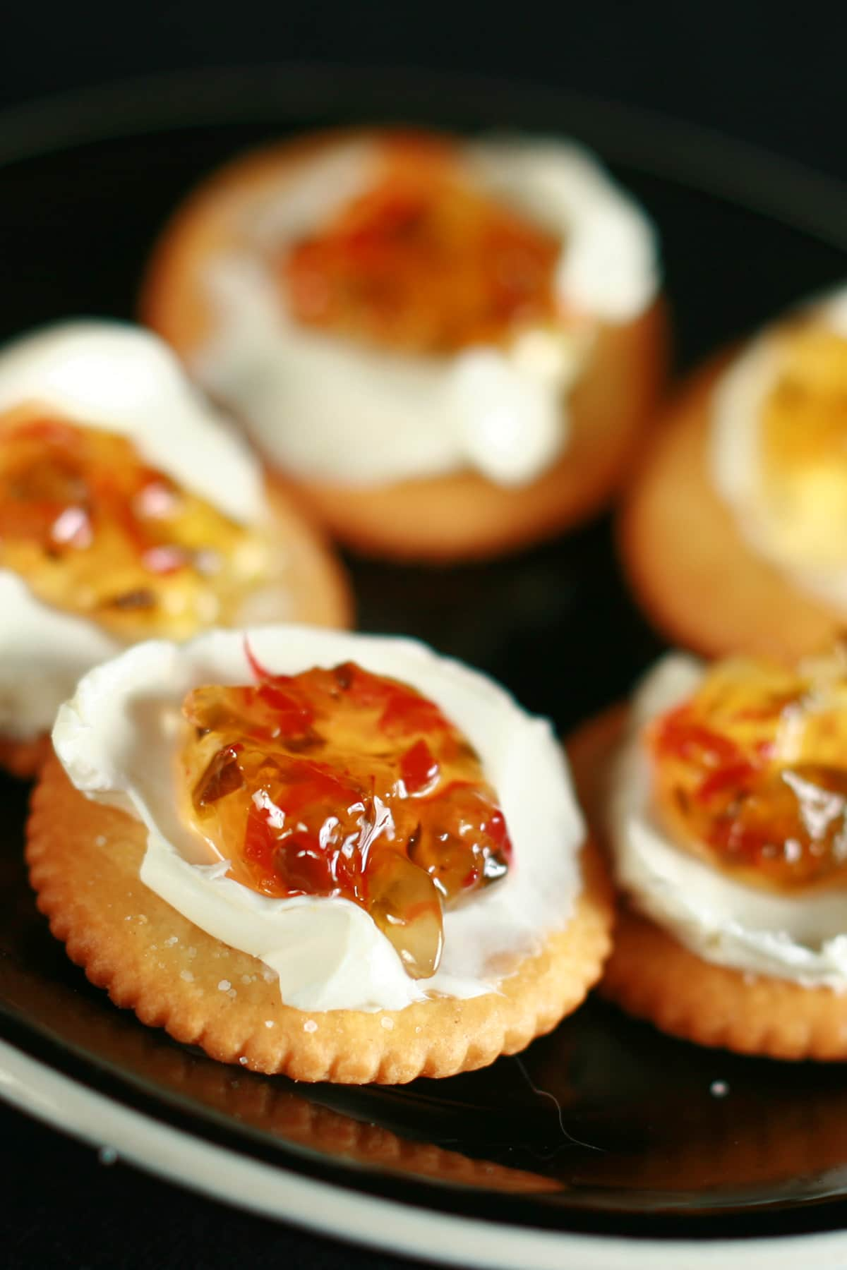 A black plate with Ritz crackers. They've been topped with a smear of cream cheese, and a dollop of pepper jelly.