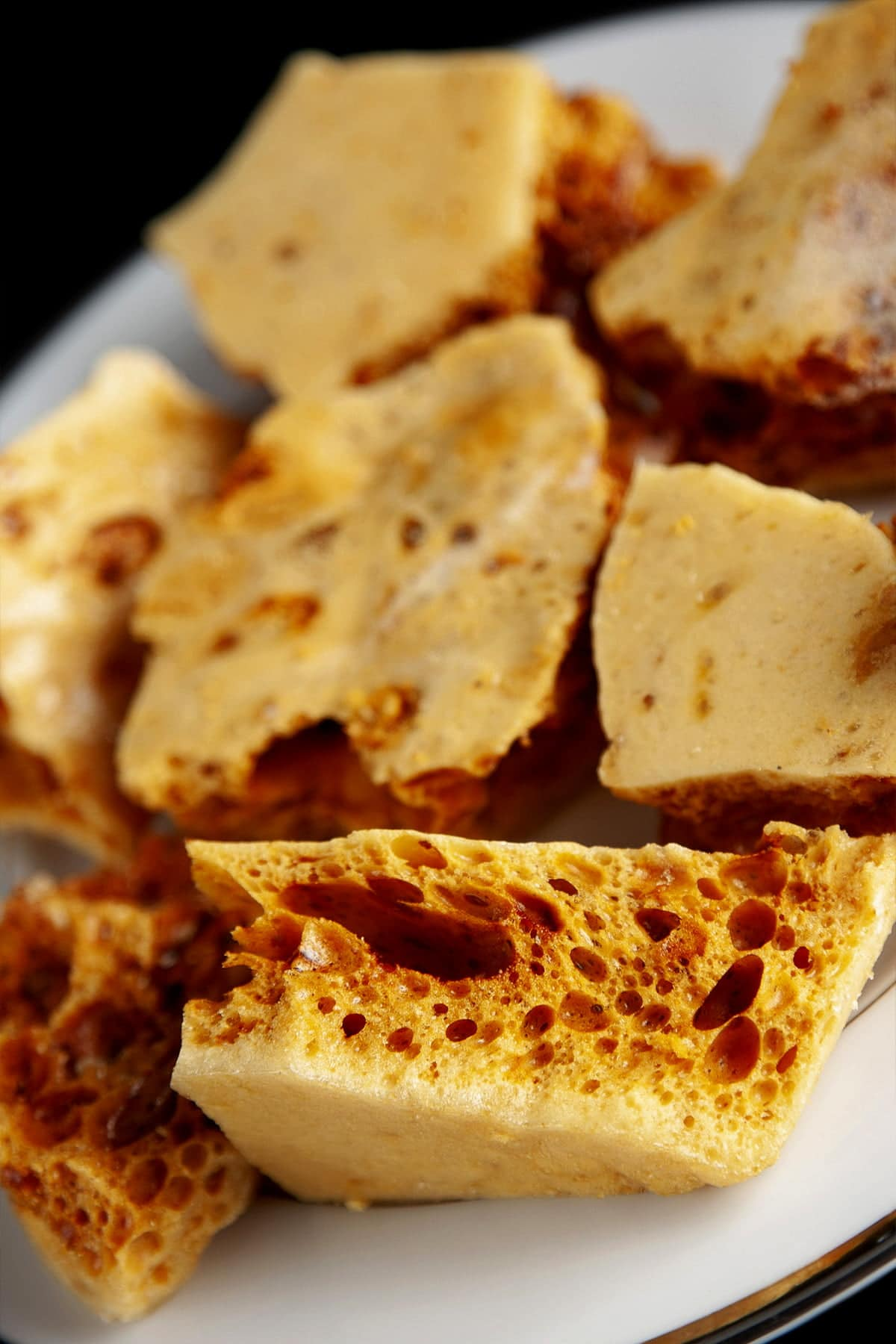Close up view of a plate of golden sponge candy chunks
