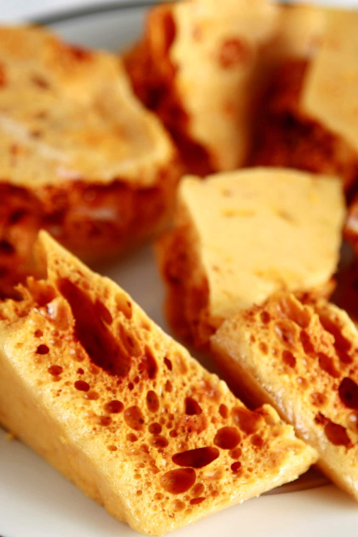 Close up view of a plate of golden honeycomb candy chunks.
