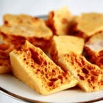Close up view of a plate of golden honeycomb toffee chunks.
