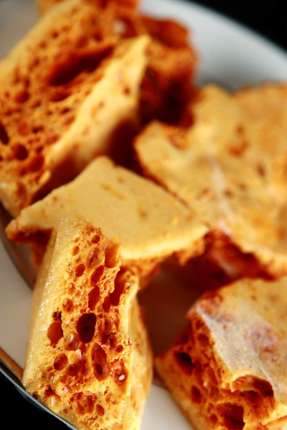 Close up view of a plate of golden sponge toffee chunks.