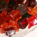 A glass bowl full of homemade jolly rancher candy -clear square shaped hard candy in orange, red, green, and purple
