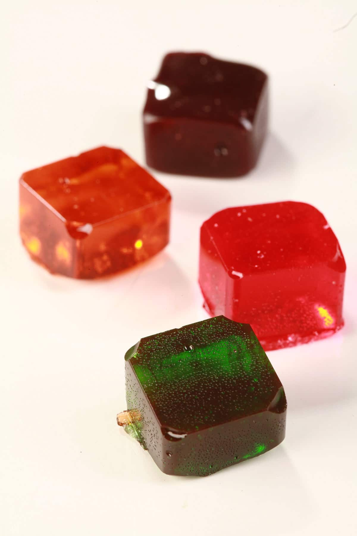 4 colourful squares of hard candy are shown on a white background.