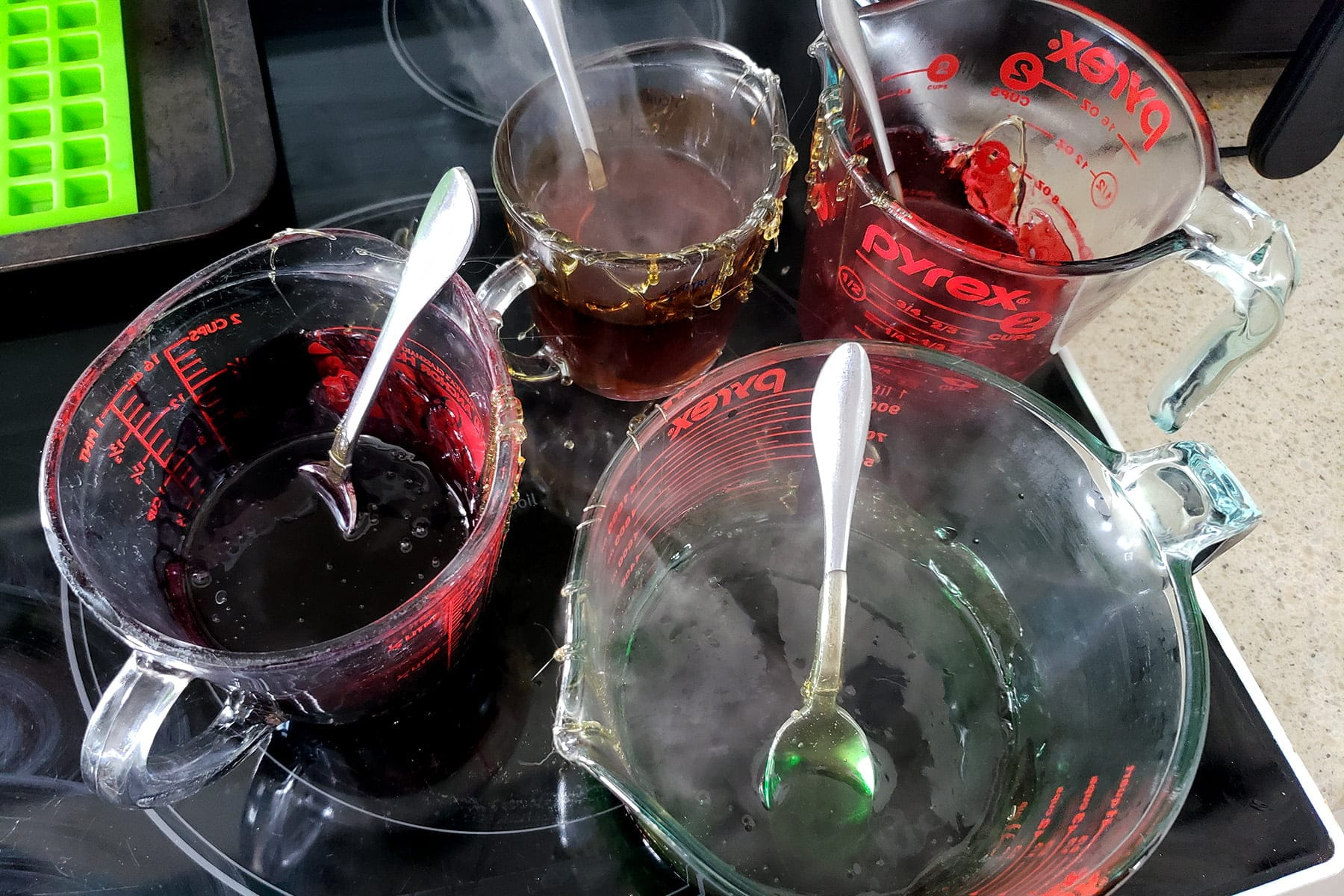 4 glass measuring cups are shown with small amounts of coloured liquid in each.
