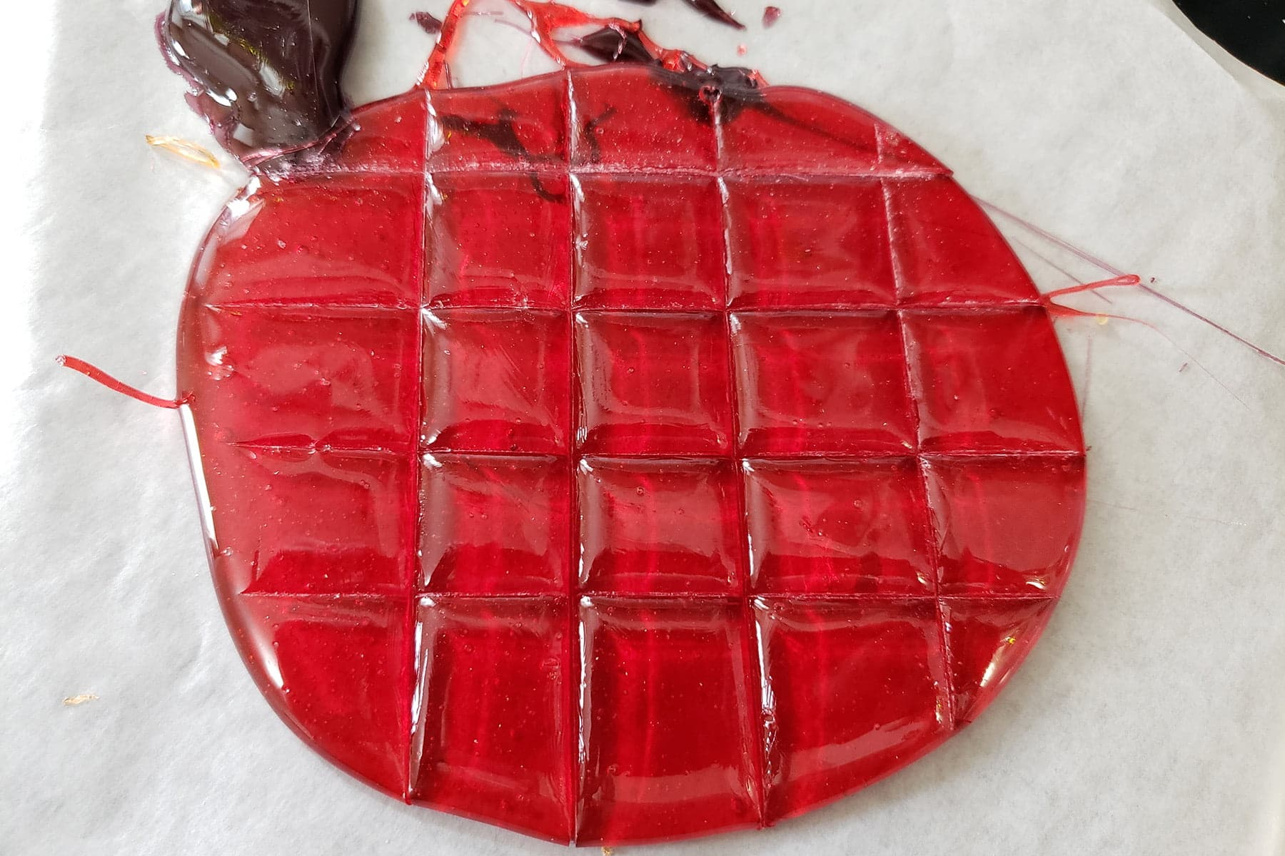A red round of hard candy is shown with score marks in a grid pattern.