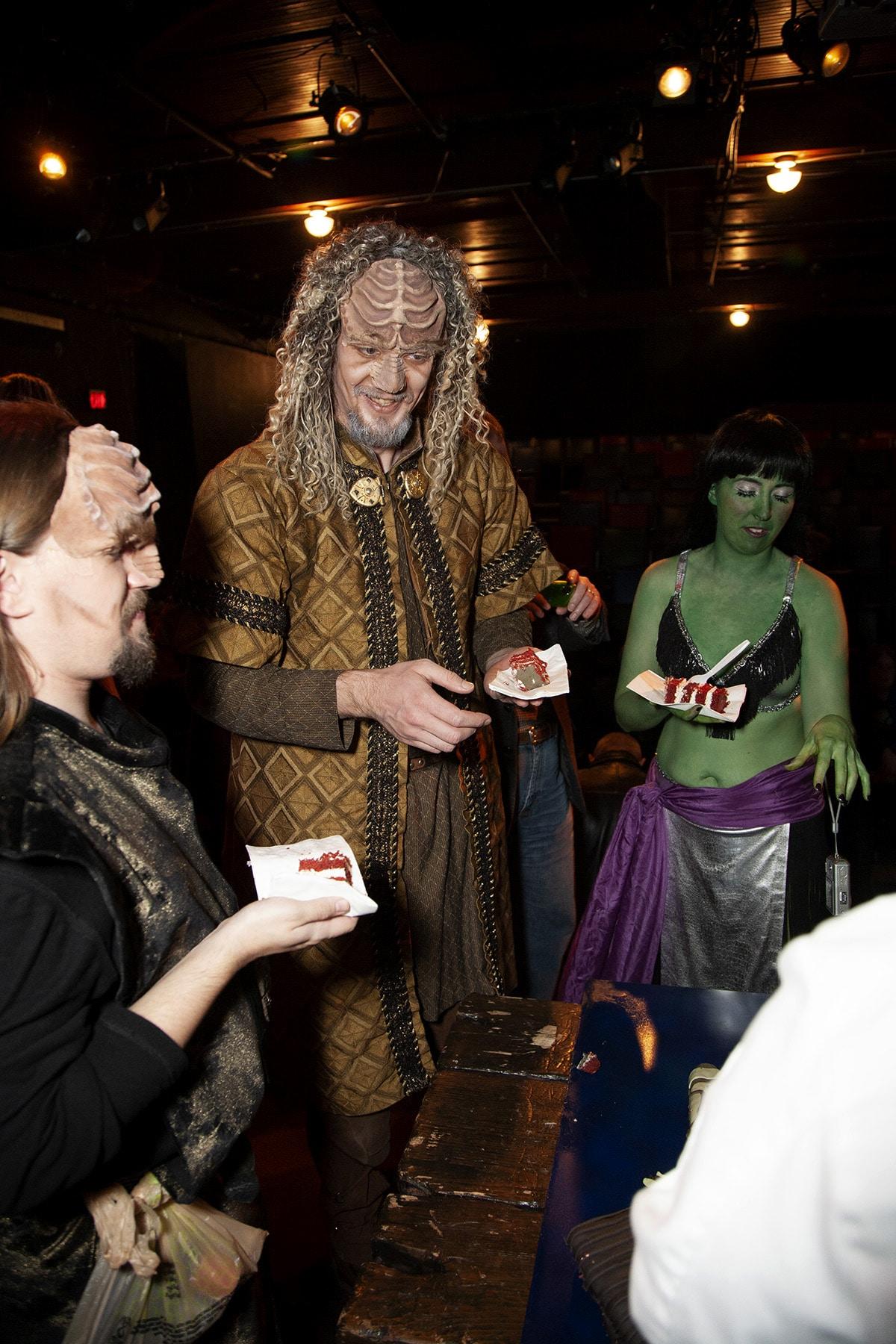 Two Klingons and an Orion slave girl enjoy slices of red velvet cake.