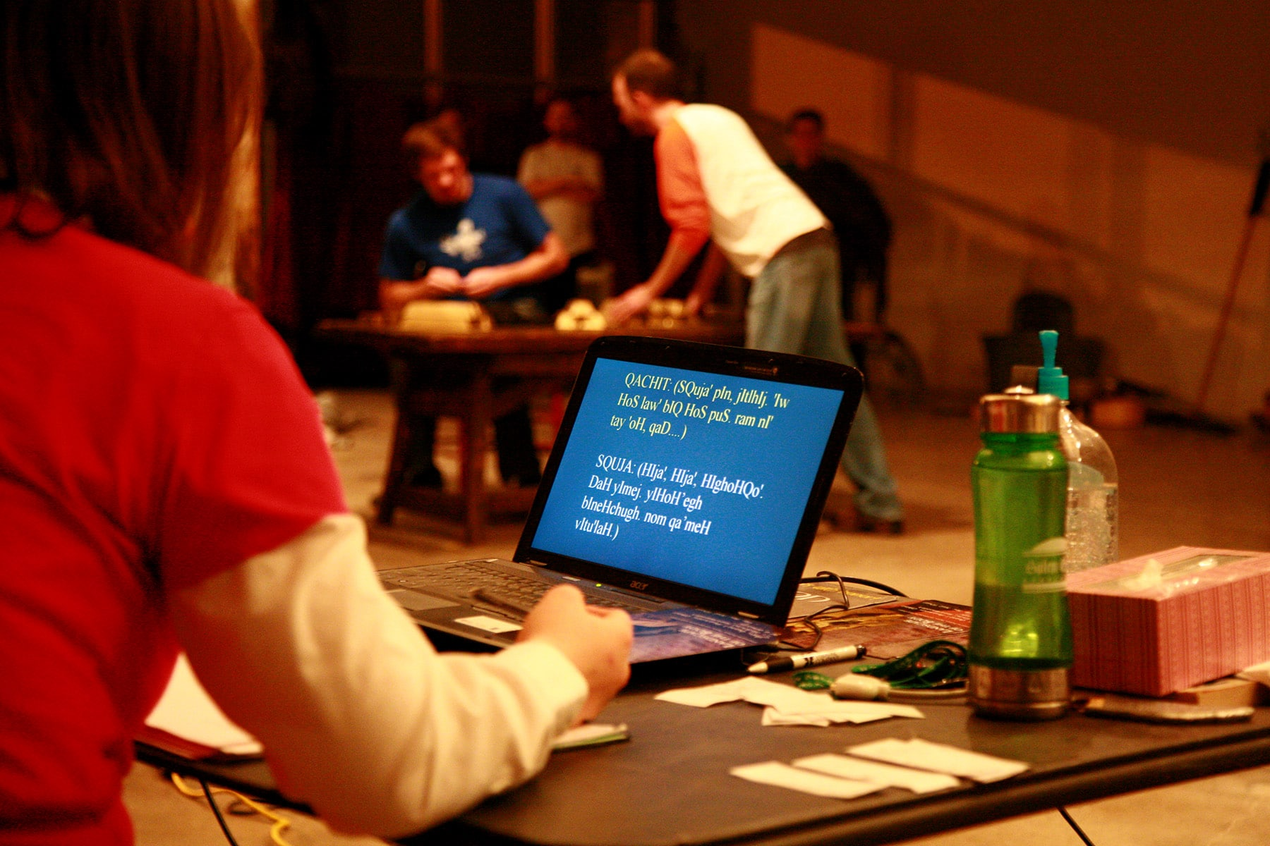 A candid theater practice photo. There is a laptop screen in view, with Klingon language across it.