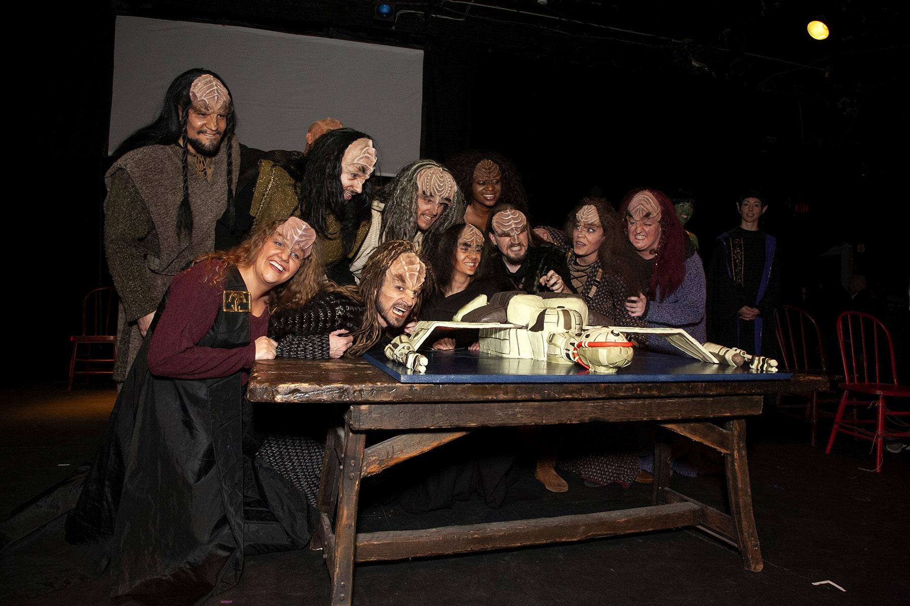 A group of Klingons gathered around a table. on the table is the Klingon ship cake.