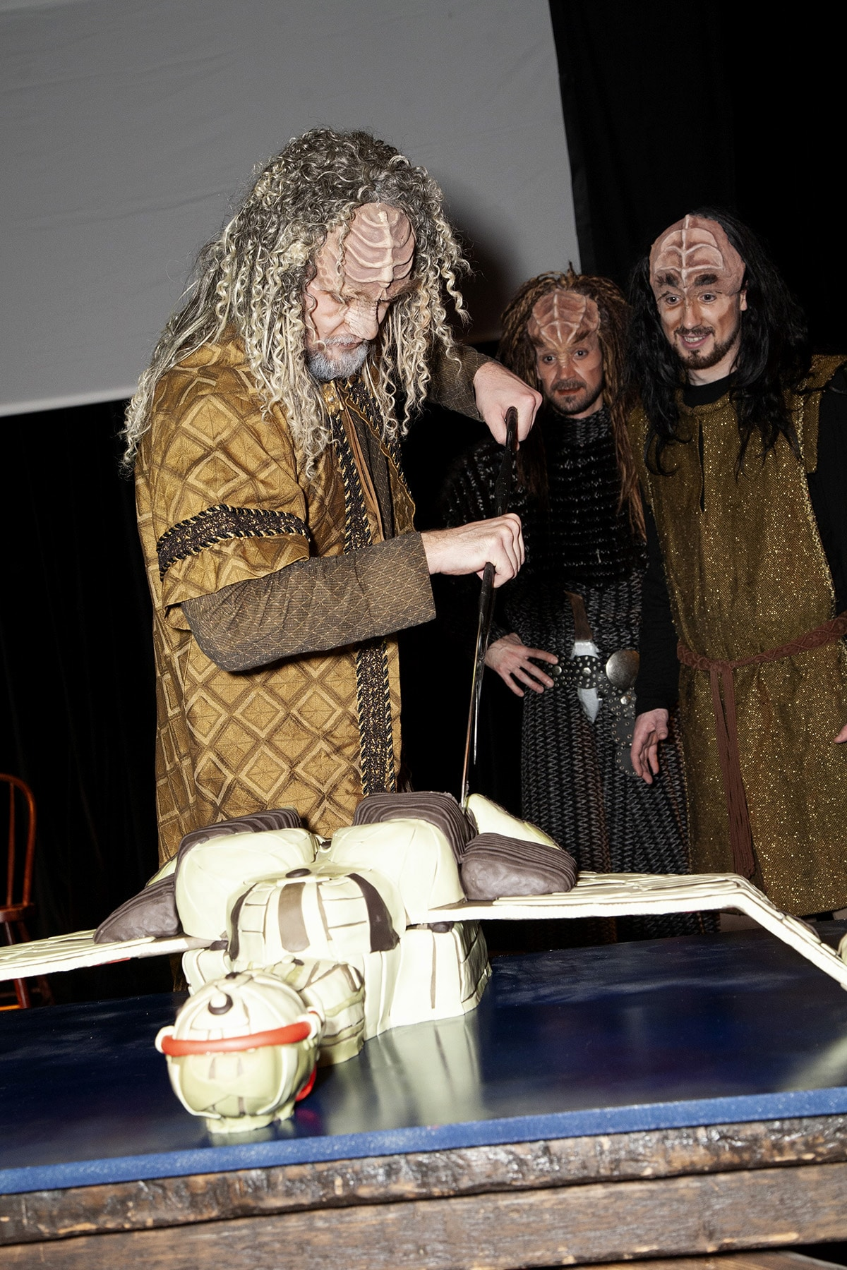 A group of Klingons gathered around a table. on the table is the Klingon ship cake. One Klingon uses his Bat'leth to cut the cake.