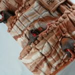 "Detail photos of a ""Tremors"" themed wedding cake, almost entirely decorated in various shades of chocolate fondant."