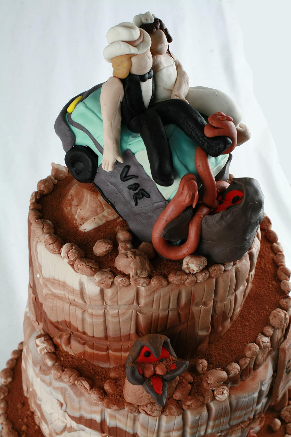 """Detail photos of a """"Tremors"""" themed wedding cake, almost entirely decorated in various shades of chocolate fondant."""
