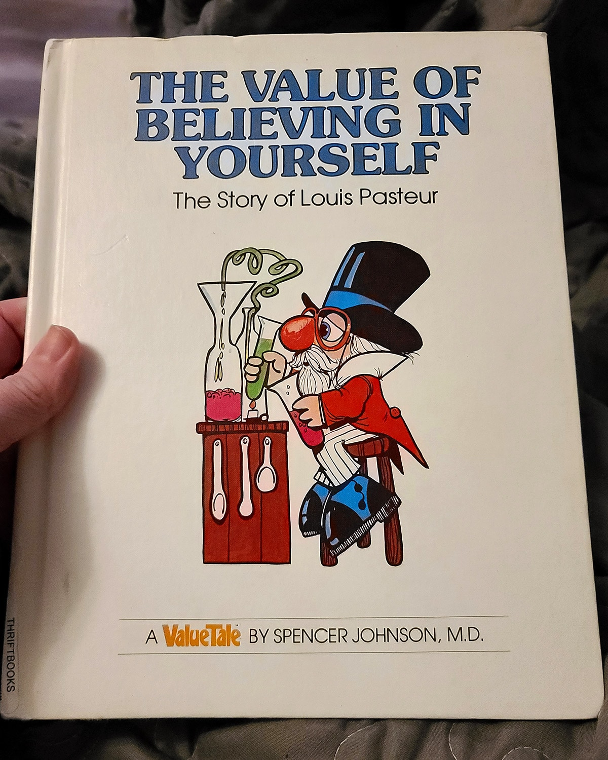 A hand holds up a copy of The Value of Believing in Yourself: The Story of Louis Pasteur.