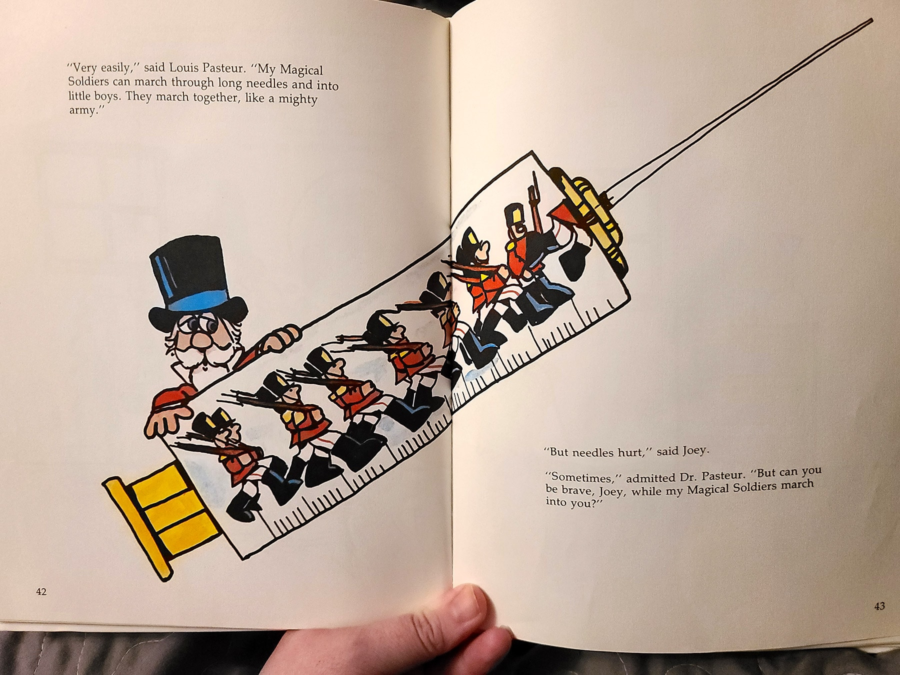 A hand holds open a children's book, it shows an illustration of soldiers in a giant needle.