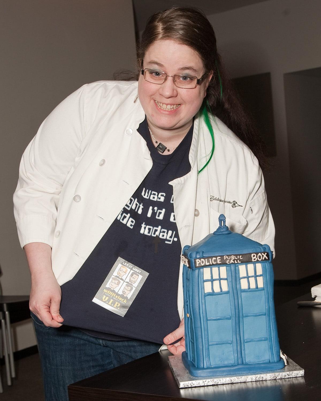 Marie Porter posing with the TARDIS cake.