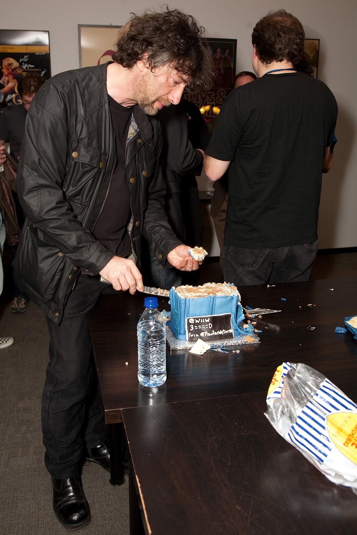 Neil Gaiman, serving himself a piece of TARDIS Cake.