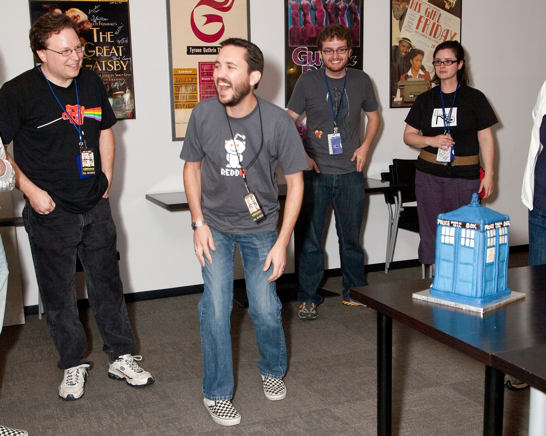 Wil Wheaton, hands on his legs, laughing as he sees the TARDIS cake.