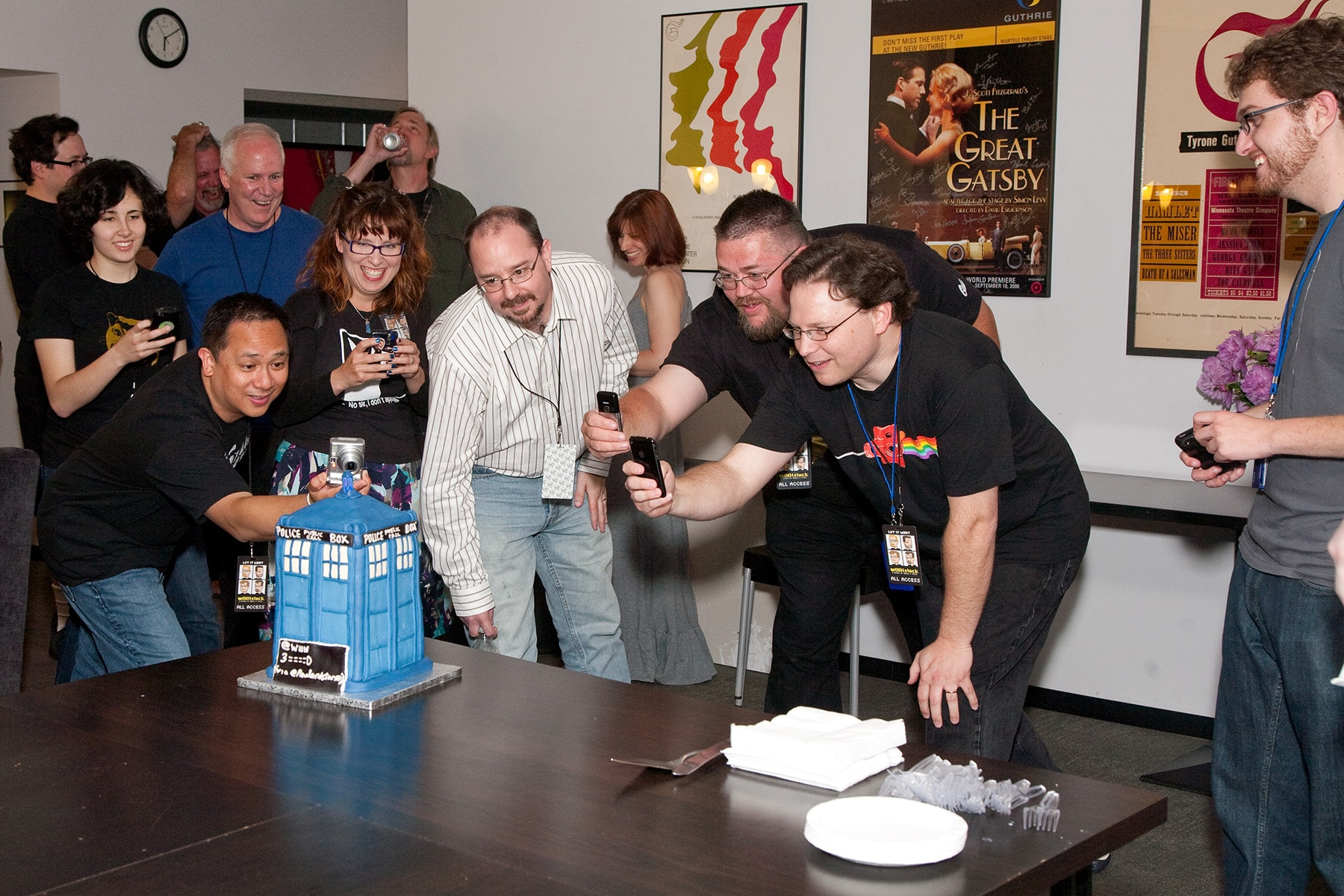 A group of nerds taking photos of a TARDIS cake.