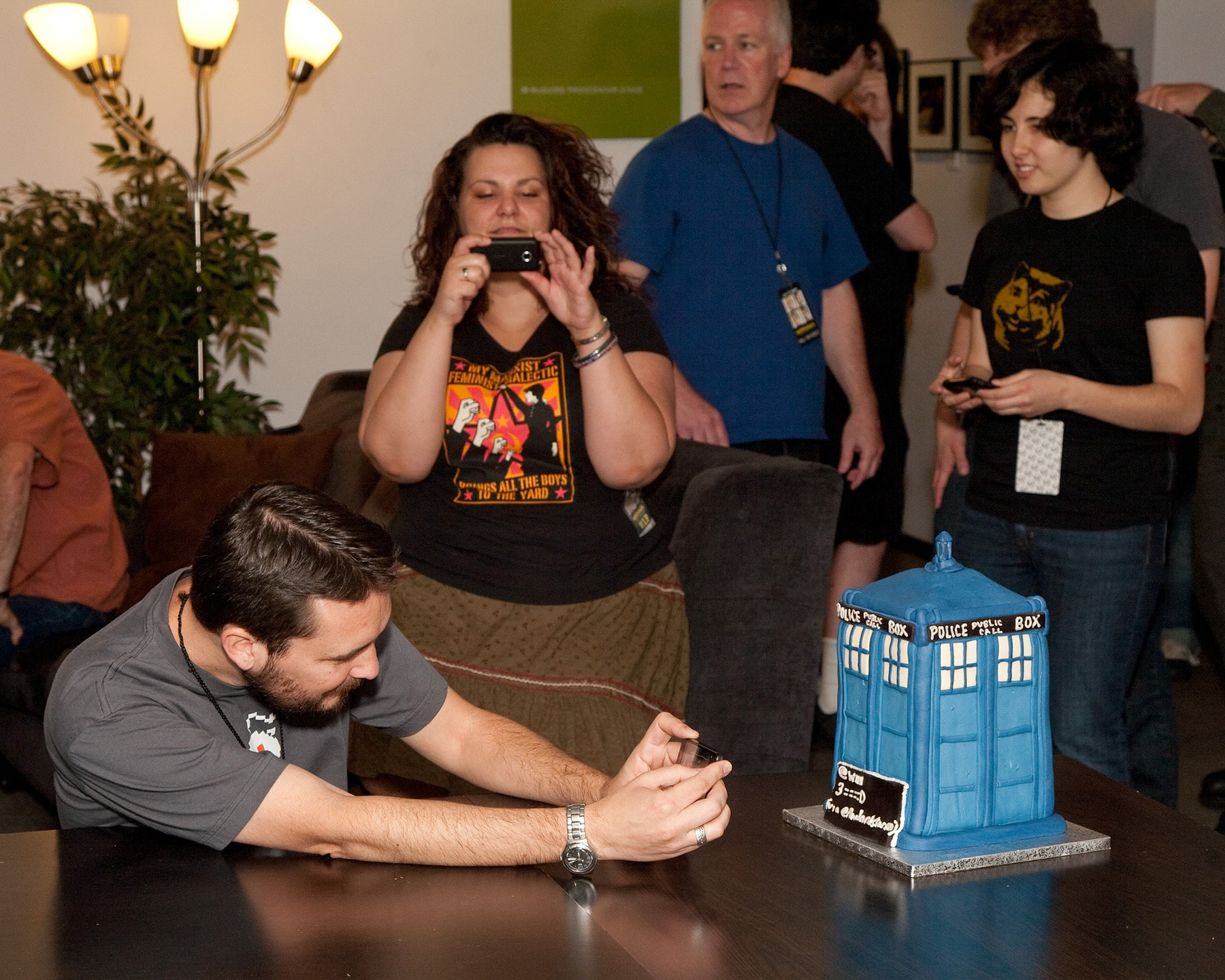 Wil Wheaton leaning on a table, taking a photo of the TARDIS Cake.
