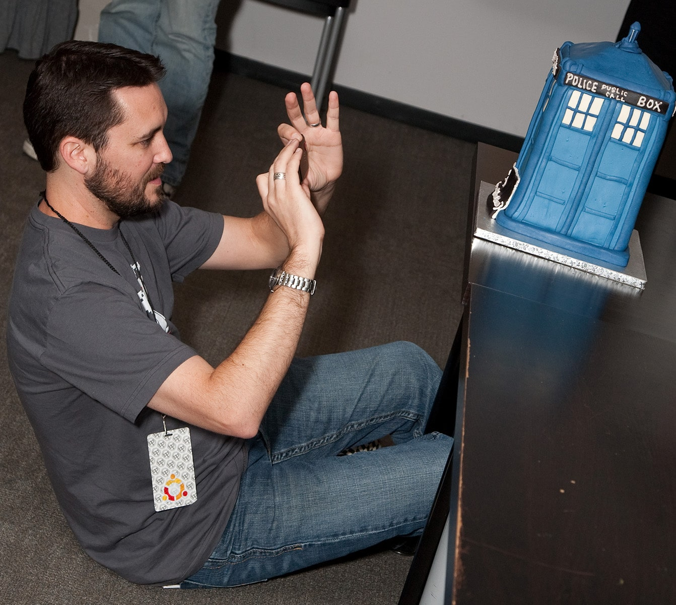 Wil Wheaton under a table, taking a photo of the TARDIS Cake.