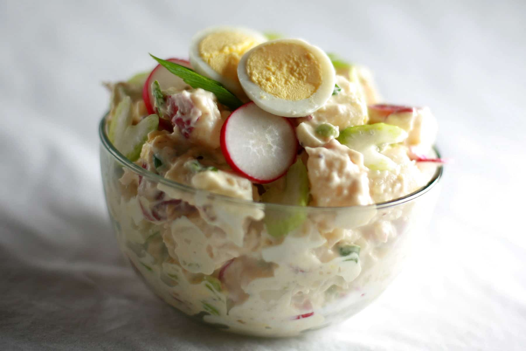 A bowl of Gramma's Potato Salad - a creamy potato salad with slices of celery, radish, green onion, and hardboiled egg visible.