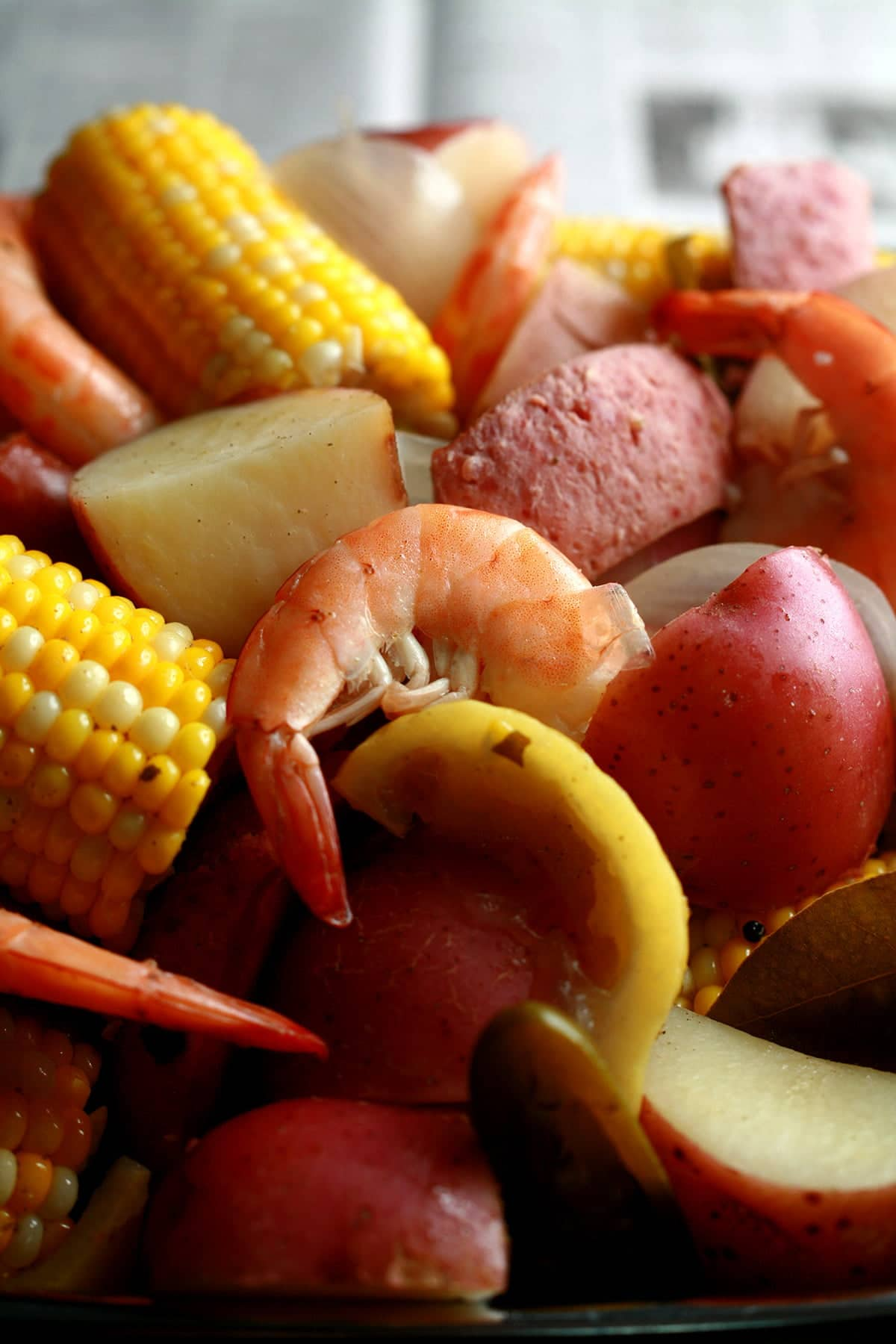 A close up view of a batch of low country boil: Red potatoes, corn on the cob, shrimp, and sausage.