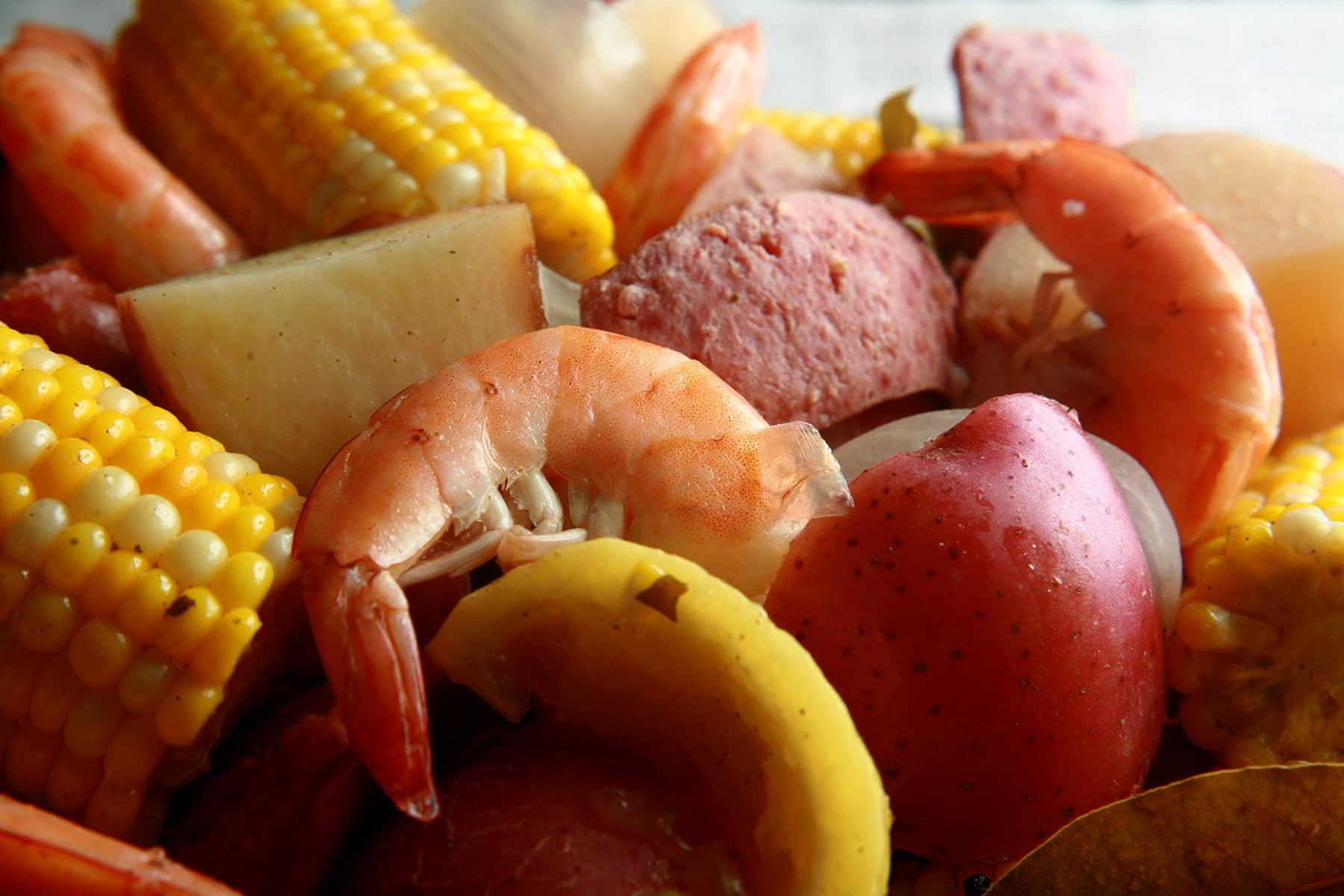 A close up view of a batch of frogmore stew: Red potatoes, corn on the cob, shrimp, and sausage.