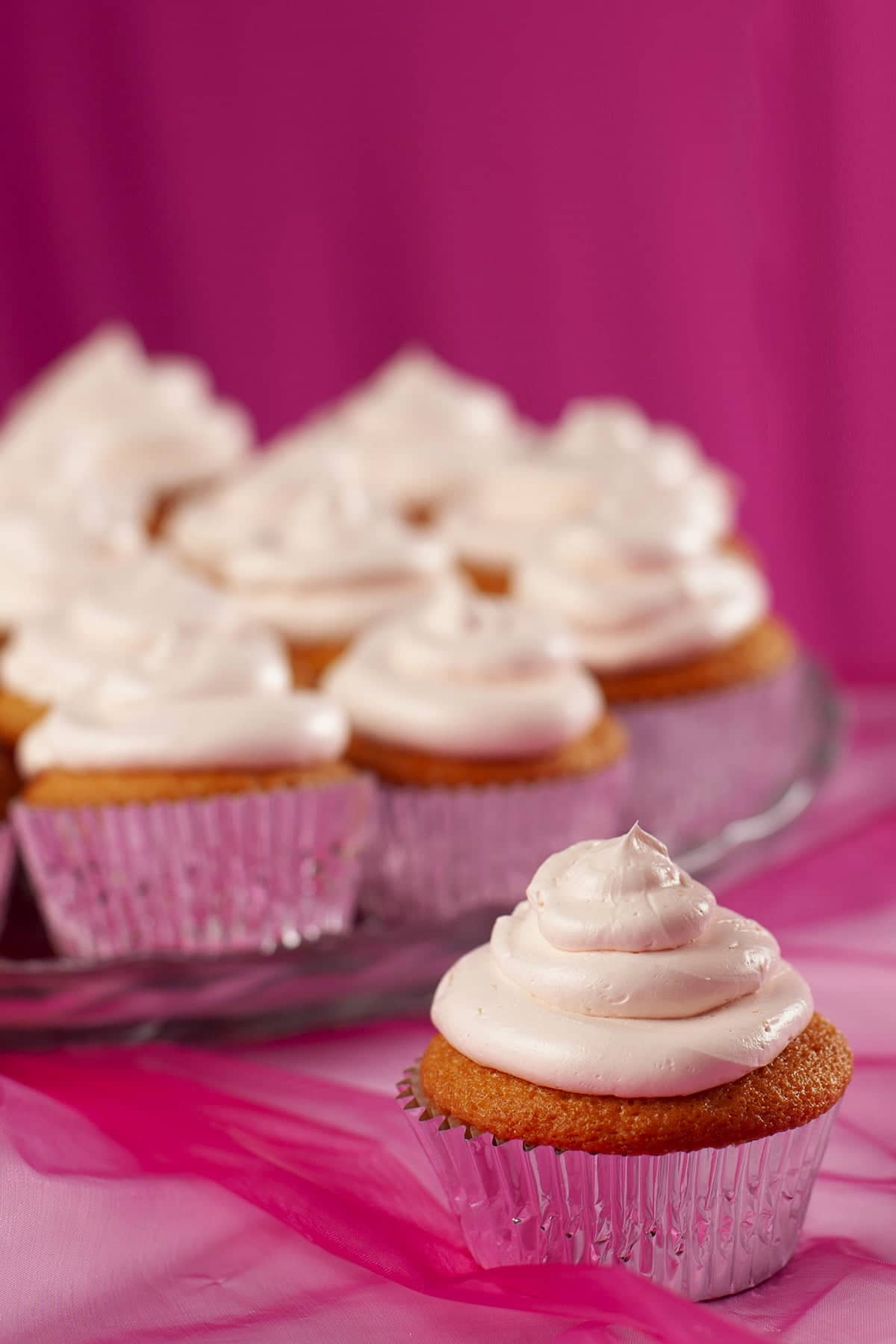 A tray of pink grapefruit daiquiri cupcakes - in silver liners, topped with pink frosting.