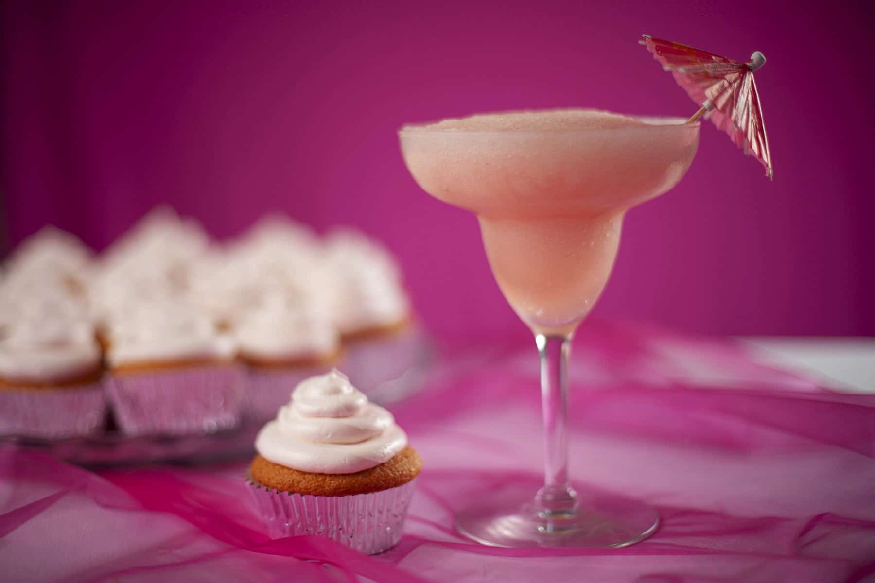 A tray of pink grapefruit daiquiri cupcakes - in silver liners, topped with pink frosting. There is a pink grapefruit daiquiri next to the cupcakes.
