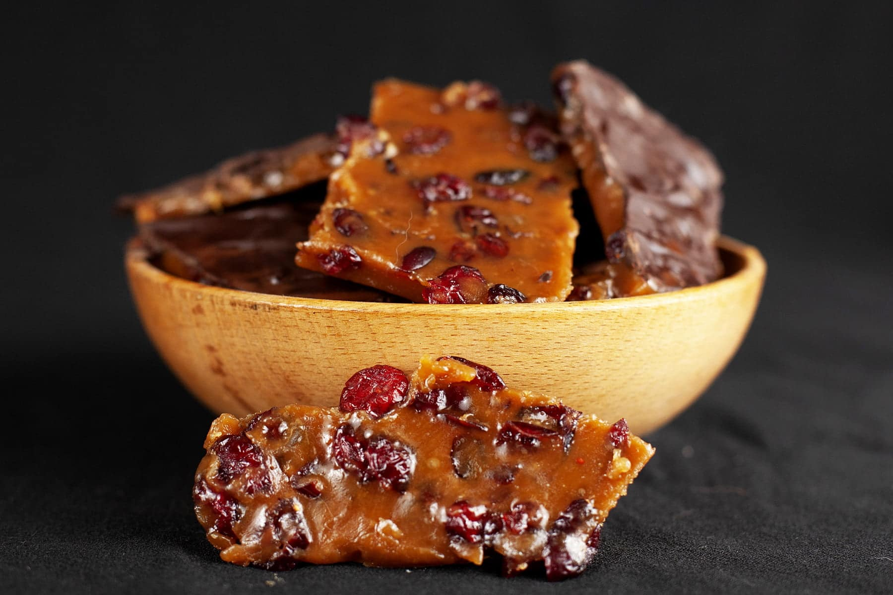 A small wooden bowl with slabs of orange-brown toffee in it. There are dried cranberries throughout the toffee, and some slabs have a layer of chocolate on top.