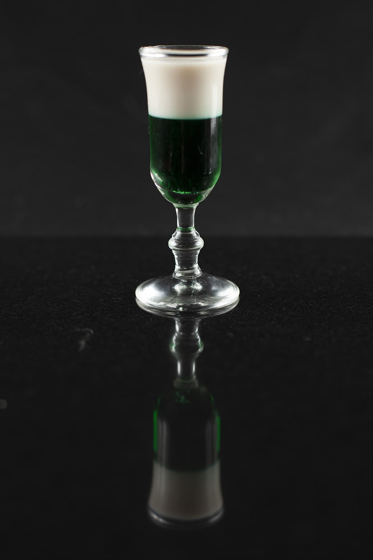 A green and black layered shot cocktail in a stemmed glass.