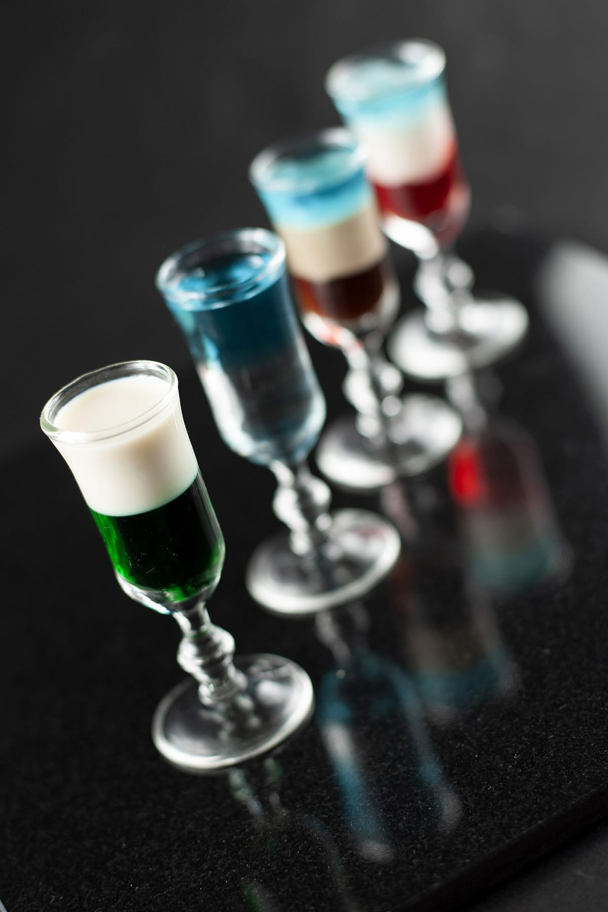 A line of multicoloured layered shooters in stemmed shot glasses.