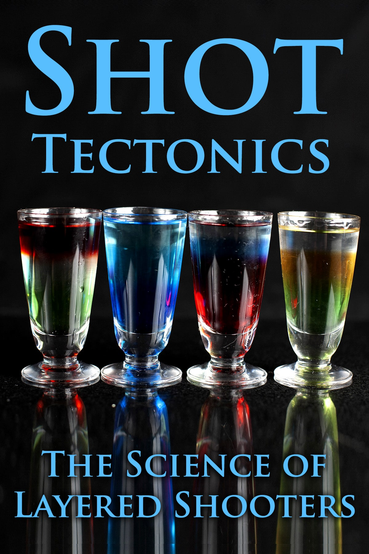 A line of multicoloured layered shooters in stemmed shot glasses. Blue text overlay says shot tectonics, the science of layered shooters.