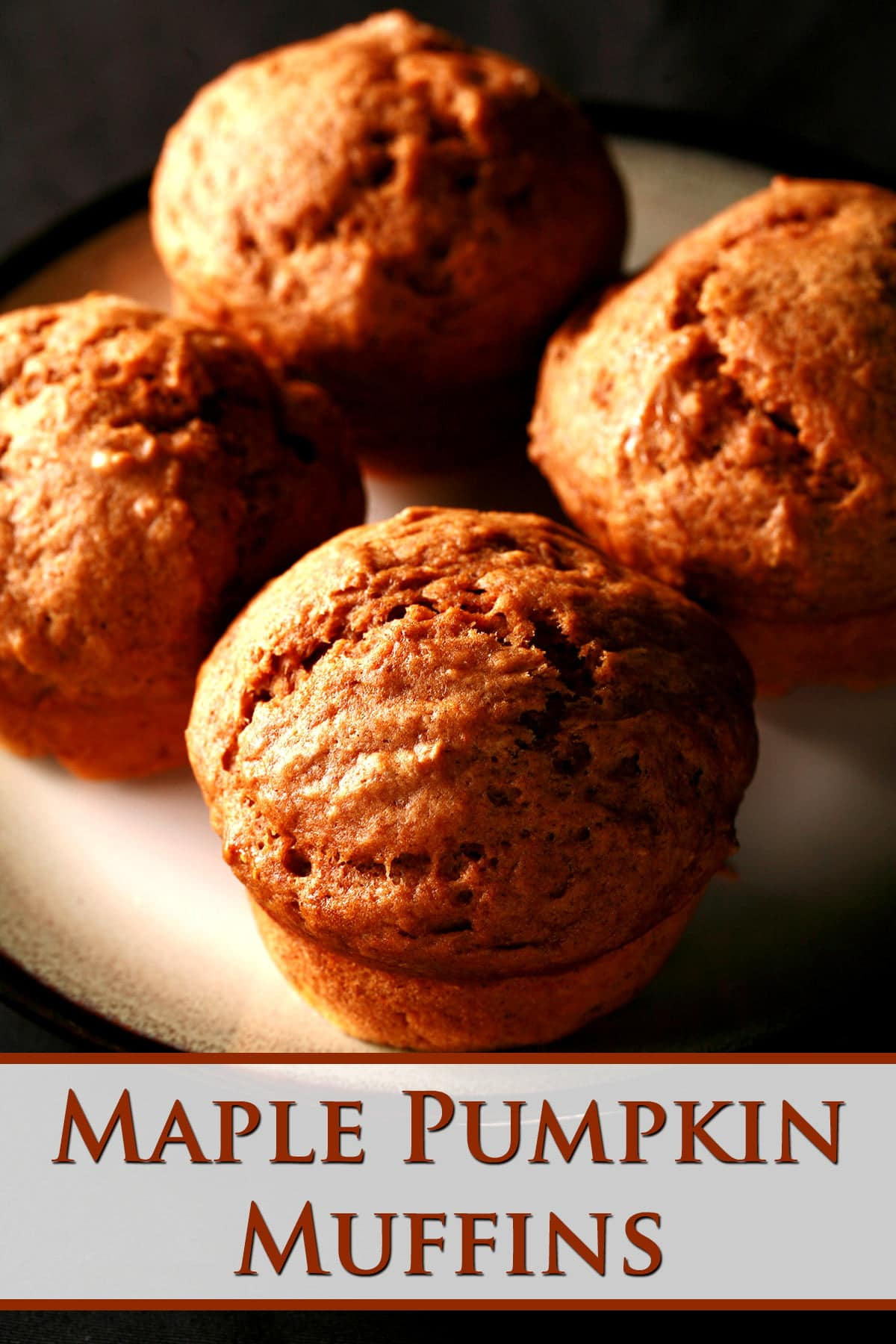 4 maple pumpkin spiced muffins are arranged on a small white plate.