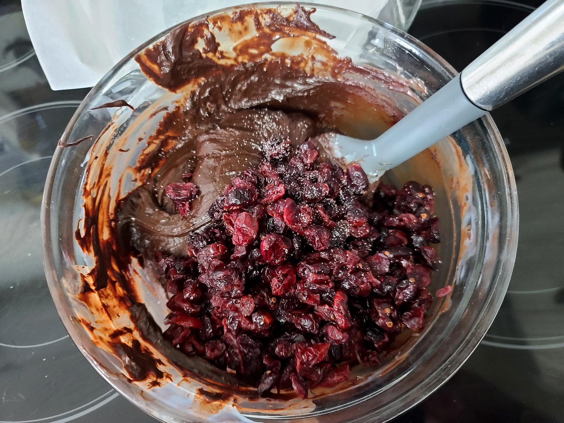 Cranberries and oramge extract being added to the fudge bowl.
