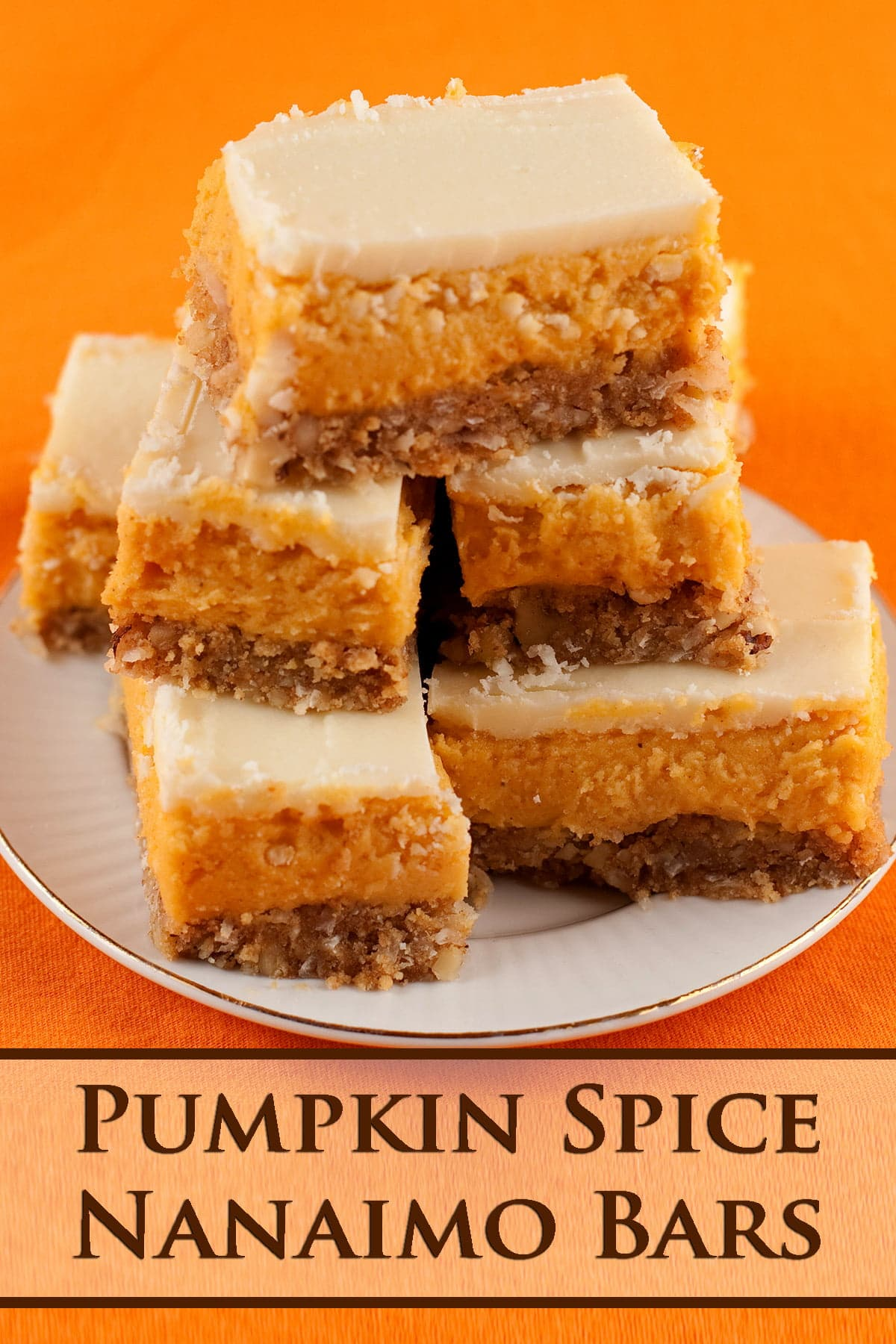 A plate of Pumpkin Nanaimo Bars - 3 layered bars. The bottom layer is a graham cookie coloured base, the middle is an orange - pumpkin - buttercream, and it is topped off with white chocolate gamache.