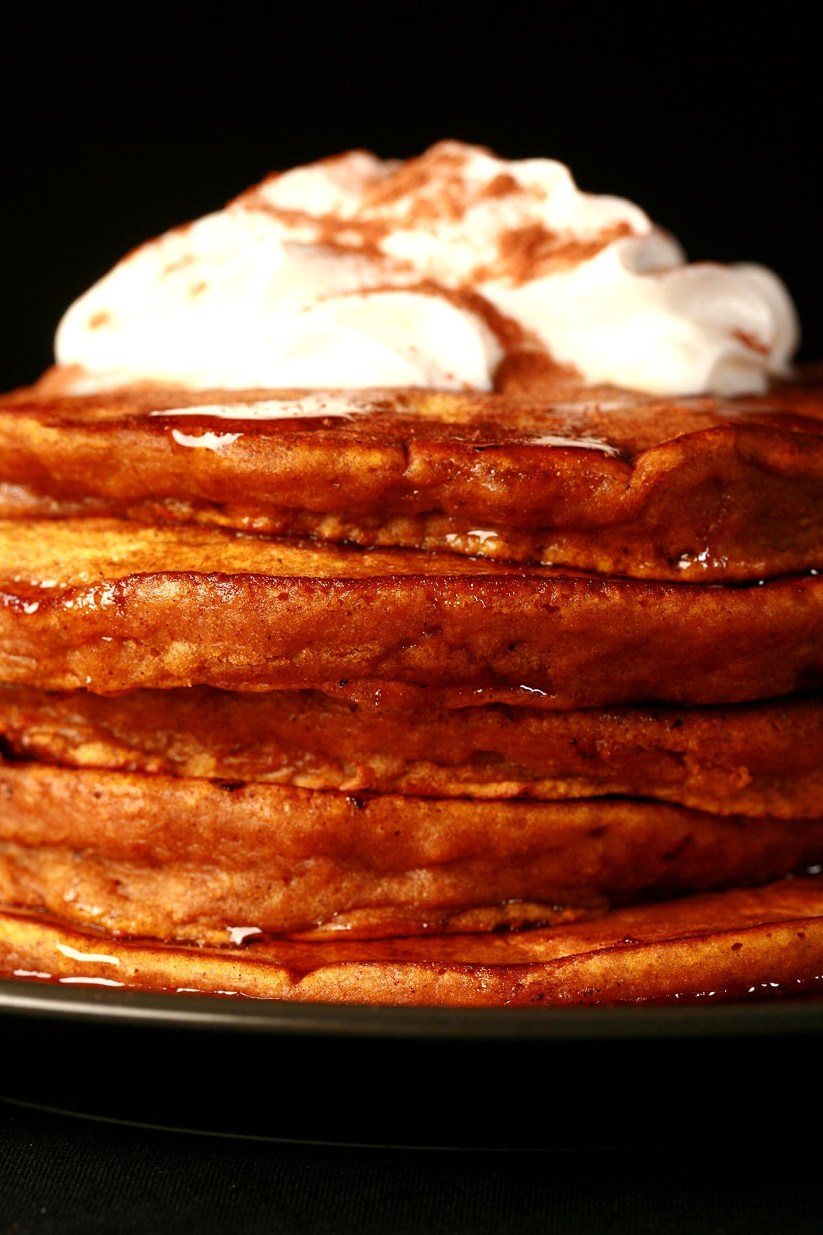 A tall stack of pumpkin pancakes, topped with whipped cream and cinnamon.
