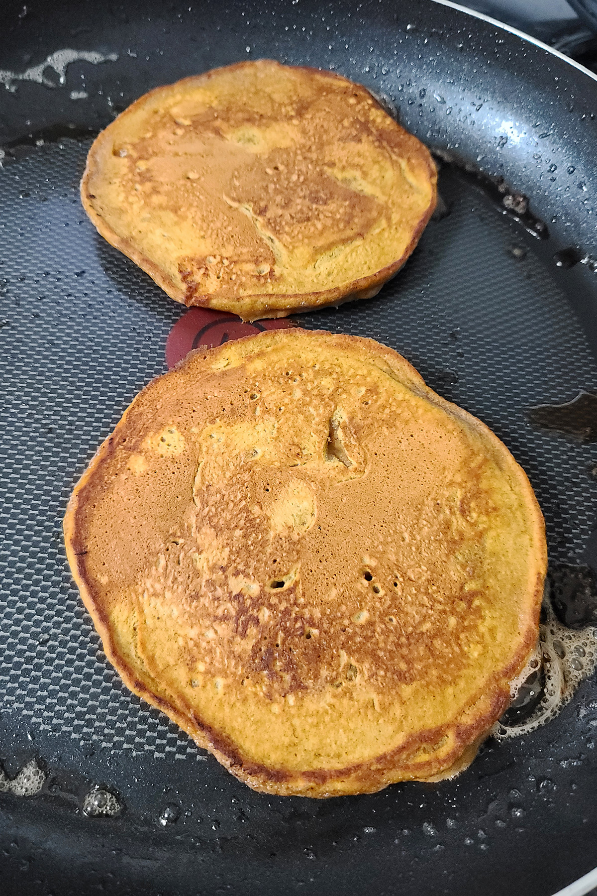 Pumpkin pancakes in a pan.
