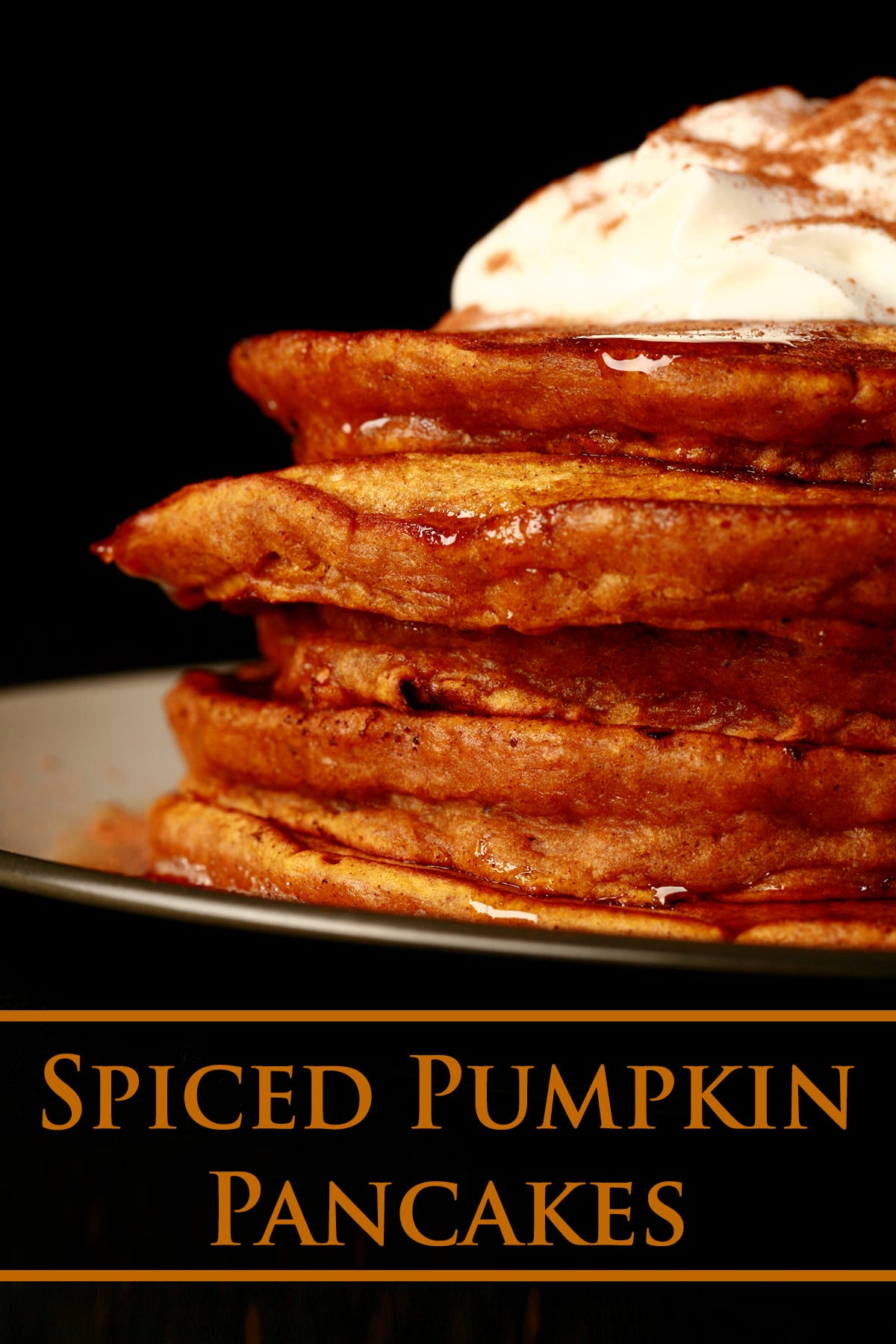 A tall stack of pumpkin spiced pancakes, topped with whipped cream and cinnamon.