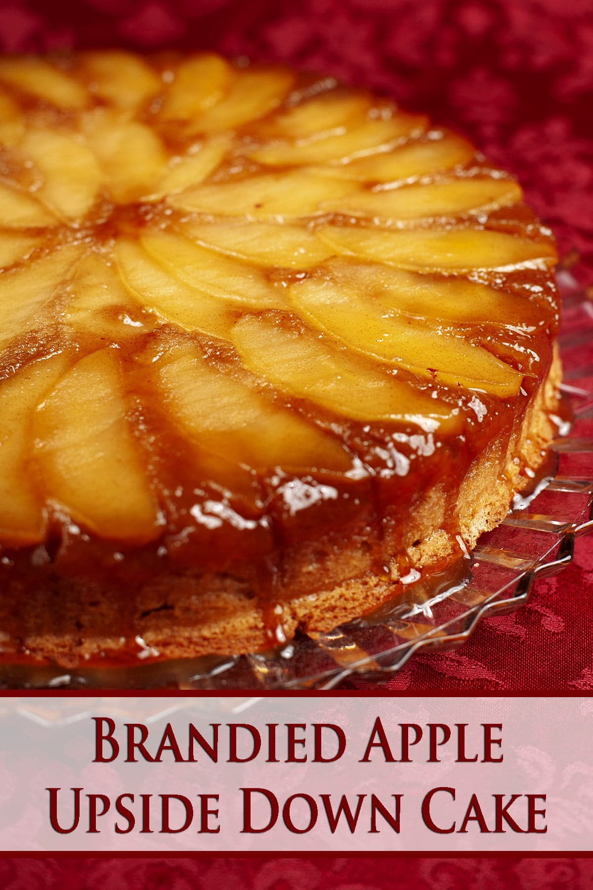 An apple upside down cake, with caramel dripping down from the top edge. It's against a burgundy fabric background.