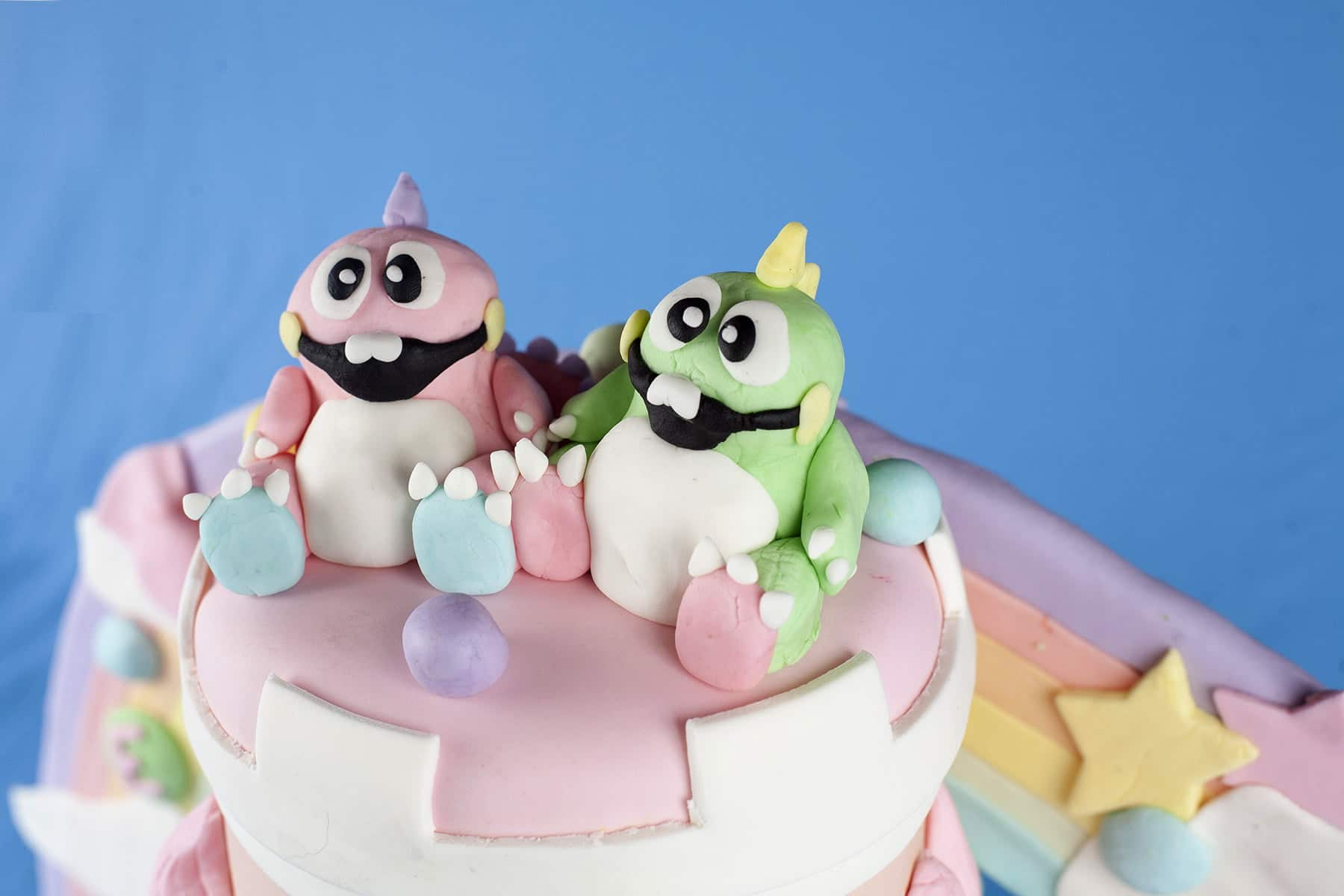 "Detailed shots of a Bubble Bobble themed wedding cake. It's 3 tiers of pinks, whites, and pastel colours, ""candy"", cartoon dinosaurs, and more."
