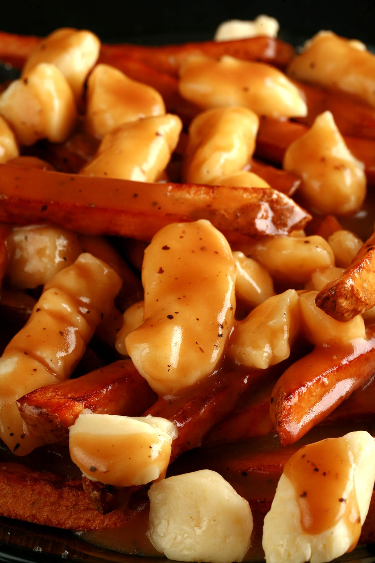A close up view of poutine - fries, white cheese curds, and gravy.