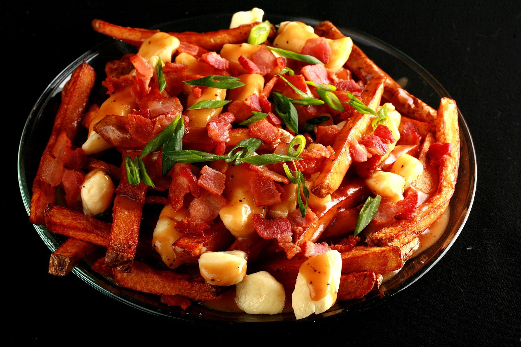 A plate of poutine - fries, white cheese curds, and gravy. This one is garnished with bacon and green onions.