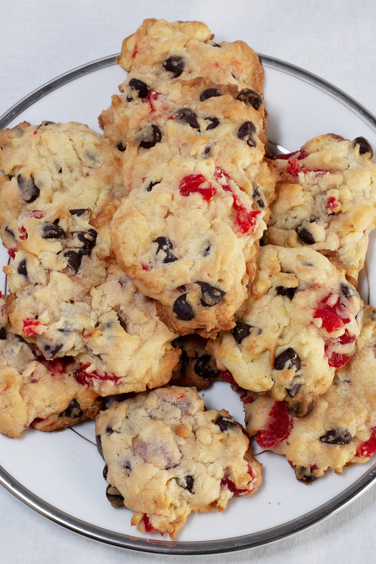 "A plate of ""Noelles"" cookies - Lighty coloured drop cookies, with chocolate chips and pieces of maraschino cherries visible."