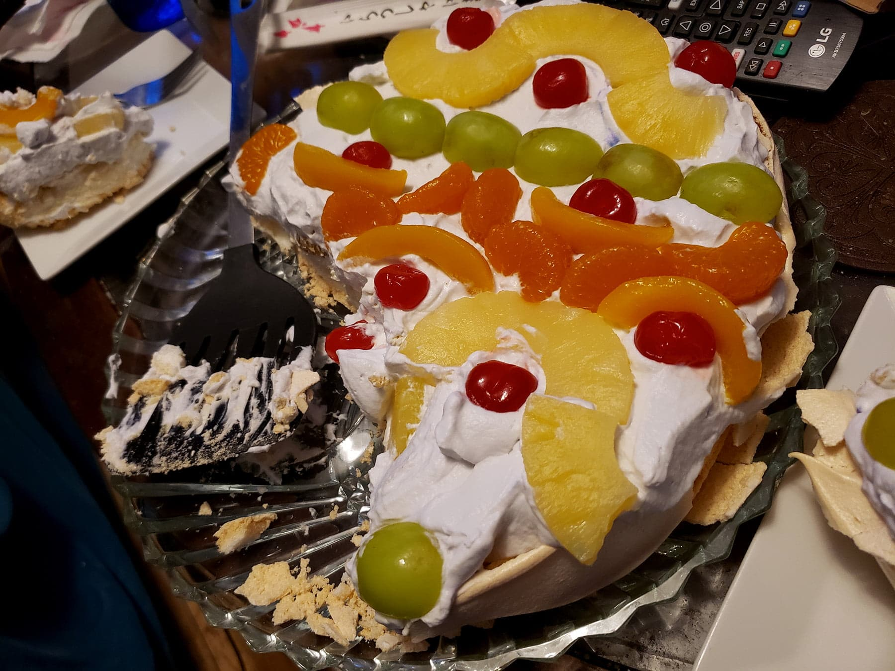 A half eaten easter egg pavlova is shown on a cluttered coffeetable.