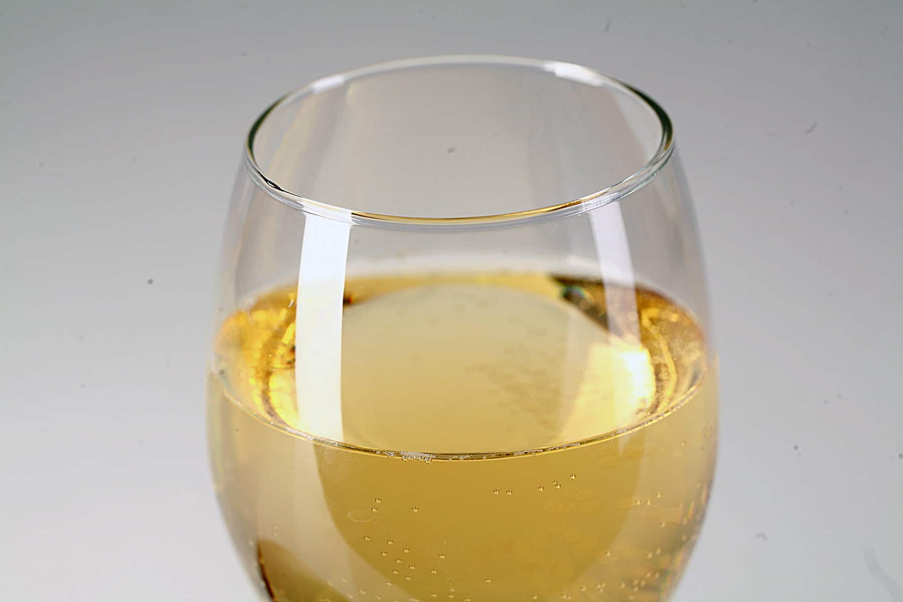 A glass of straw coloured wine is pictured next to a whole mango.