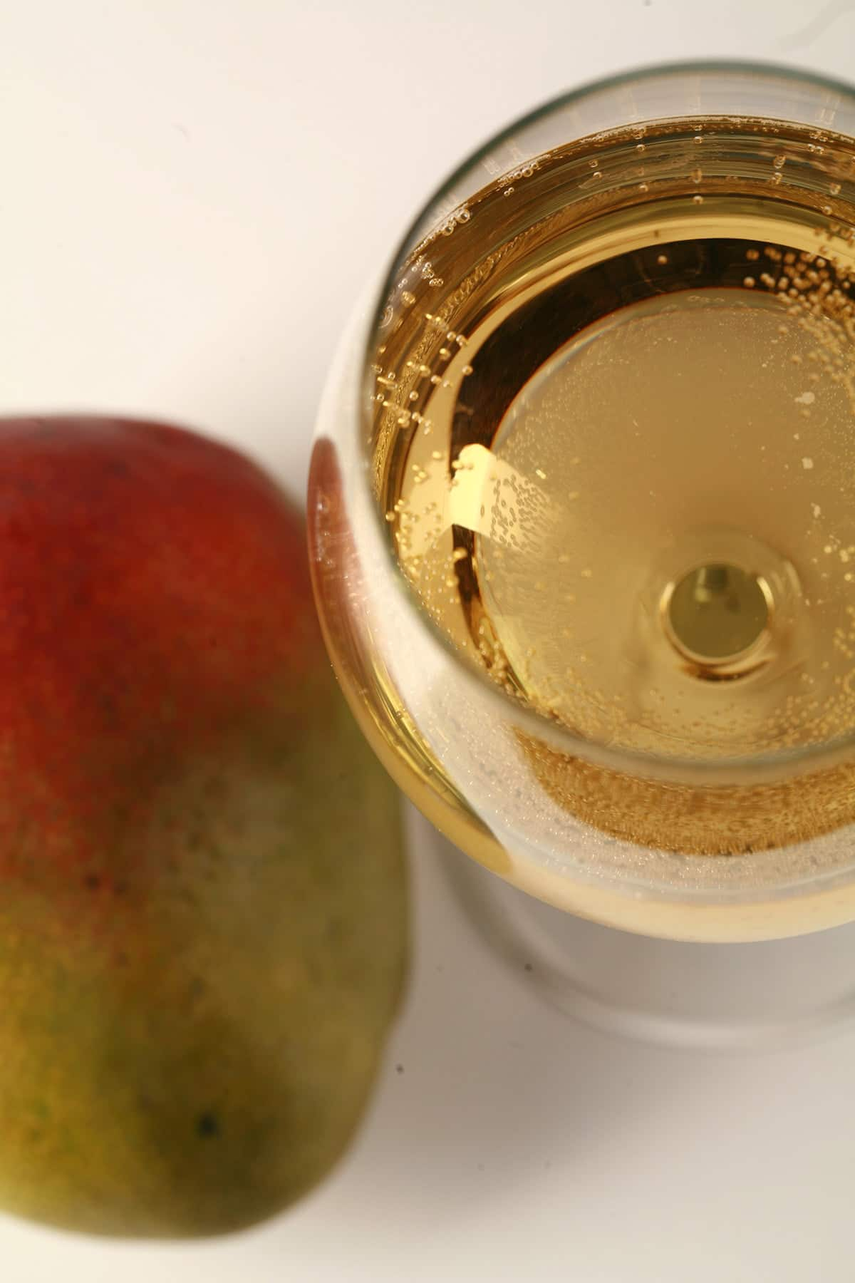A glass of straw coloured mango wine is pictured next to a whole mango.