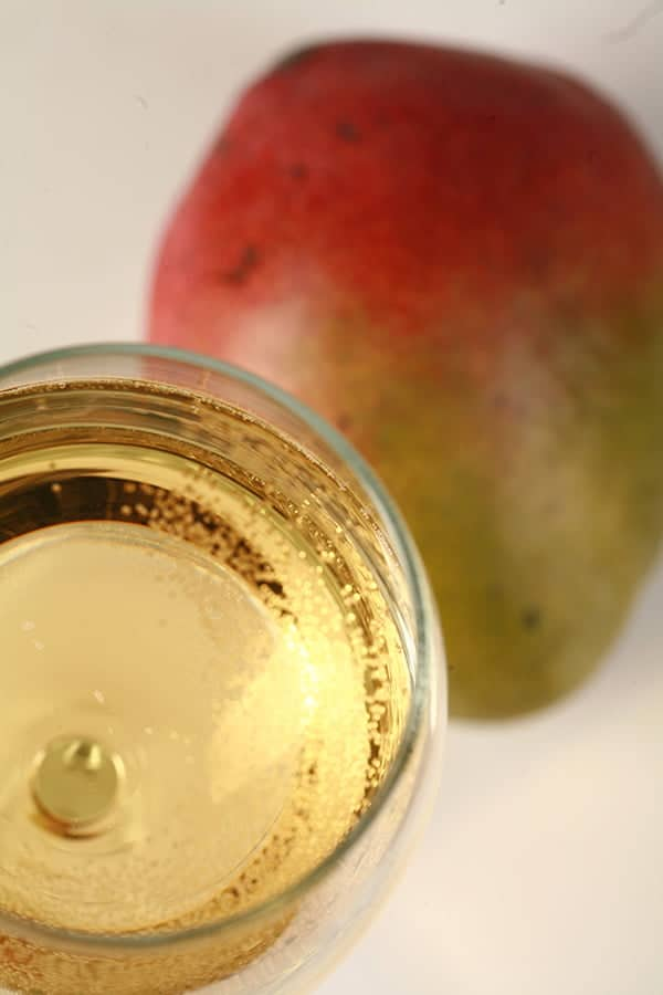 Closeup photo of a glass of pale straw coloured mango wine, next to a mango