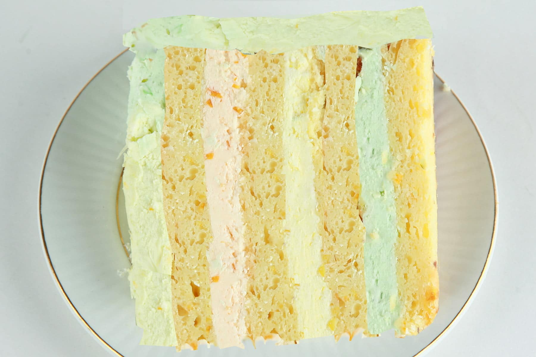 A slice of citrus splendor cake on a plate. 4 layers of a yellow citrus cake, separated by orange, lemon, and lime buttercream layers.